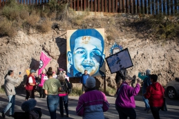 Protesters pause by the portrait of 16-year-old José Antonio Elena Rodriguez, who was shot 16 times through the U.S.-Mexico border fence in Nogales, Sonora, Mexico by border patrol in 2012. (Photo by Kailey Broussard)