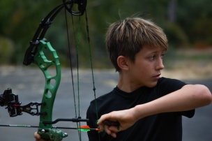 Cole looks away as he prepares one of his arrows. His family's shed and patio area doubles as his shooting range and practice hockey rink. (Kailey Broussard)
