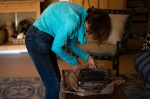 Lali Mitchell unwraps her father's typewriter. The machine is one of the few things she salvaged from the fire. (Photo by Kailey Broussard / News21)