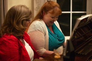 Lori Roach and Allyson Watson laughingly try to remember standard piano tunes. The piano in the Roach's home was picked with Ashleigh Roach, Watson's younger sister, in mind. Ashleigh, however, died before playing that piano. (Photo by Kailey Broussard / News21)