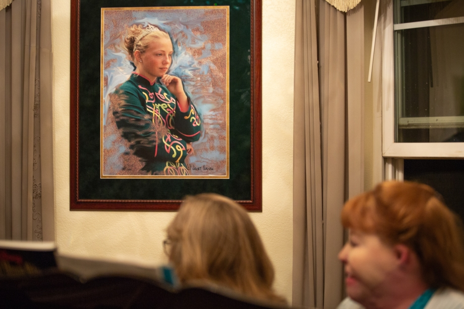 Lori Roach and Allyson Watson look over at a portrait of Ashleigh Roach, who died at 16 in the 2003 fires outside her parents' home in Valley Center. Ashleigh loved Irish step dance. (Photo by Kailey Broussard / News21)